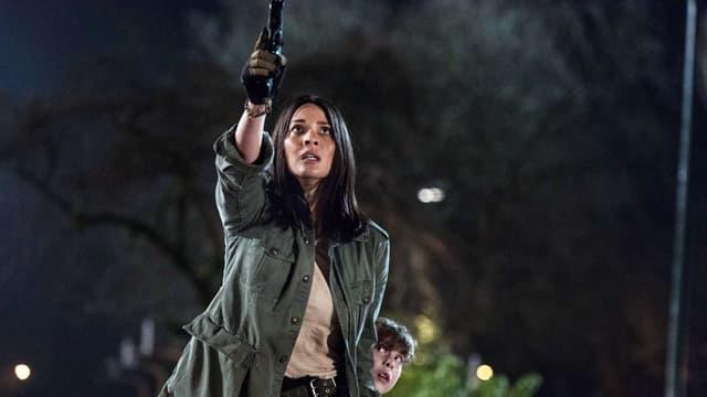 Szene in der Nacht: Eine Frau hält eine Pistole auf etwas gerichtet, das vor ihr steht. Hinter ihr schaut ein verängstigter Junge hervor.