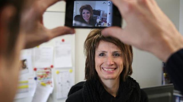 Frau wird mit Handykamera gefilmt.