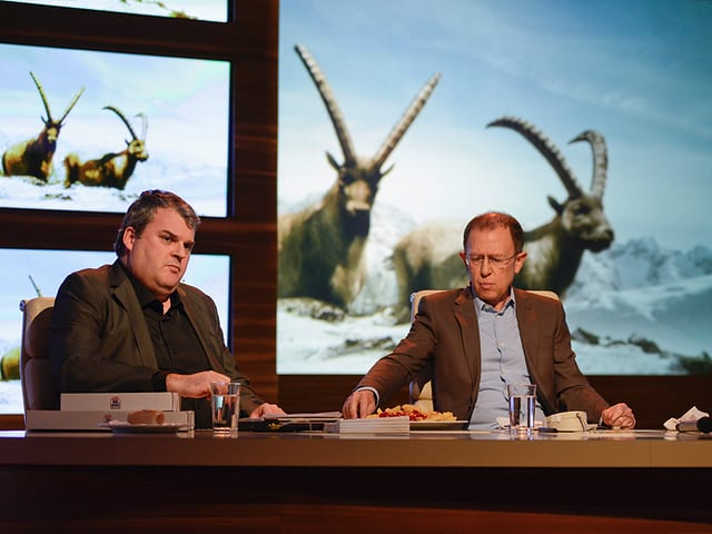 Mike Müller und Viktor Giacobbo am Essen, während die Nachsynchronisierung «Steinböcke bei Olympia» im Hintergrund gezeigt wird.