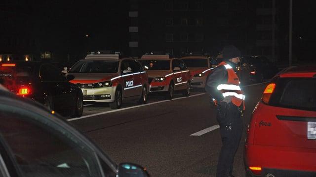 Streifenwagen in Reih und Glied, davor eine Polizistin an einem angehaltenen Auto