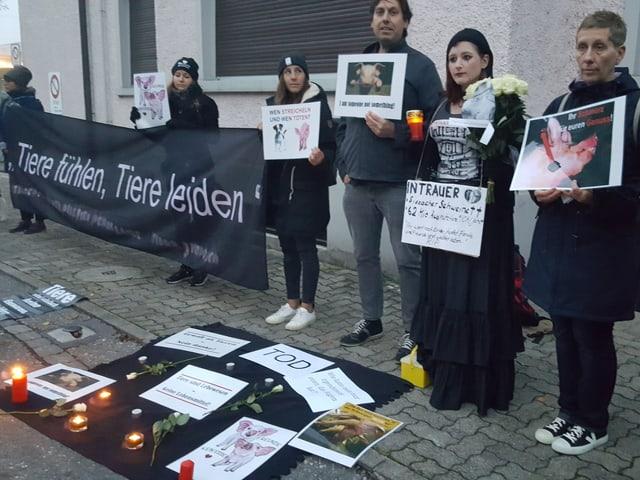 Tierschützer stehen schwarz bekleidet und mit Transparenten am Strassenrand