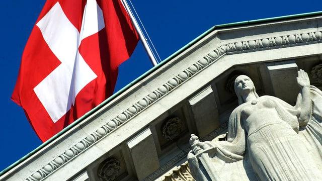 Die Schweizer Flagge weht über der Spitze des Bundesgerichts, Eine Statue ist zu sehen, die linke Hand erhoben, in der rechten ein Schwert.