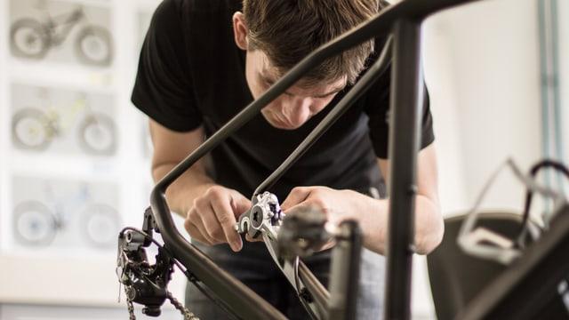 Ein Fahrradmechaniker montiert Teile an ein Mountainbike.