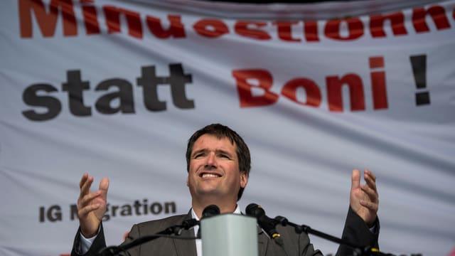 Christian Levrat spricht vor einem Plakat mit der Aufschrift «Mindestlohn statt Boni!»