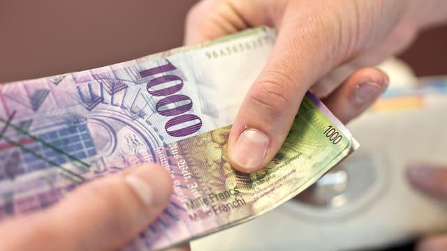 Zwei Hände übergeben sich eine Banknote im Wert von Tausend Franken.
