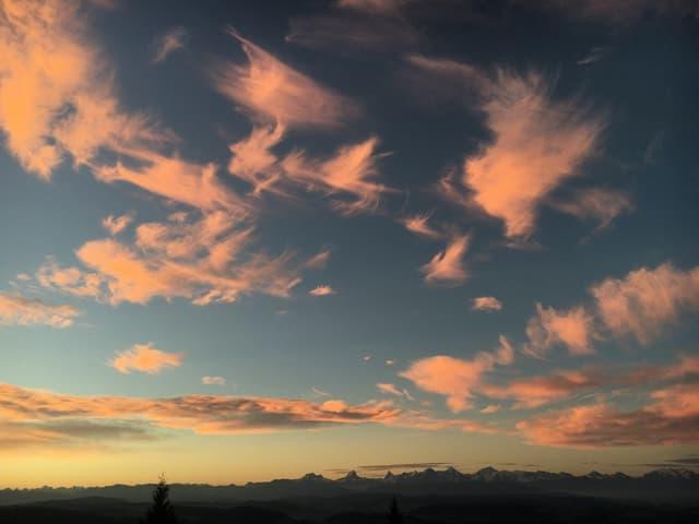 Rötliche Wolken über Alpenpanorama