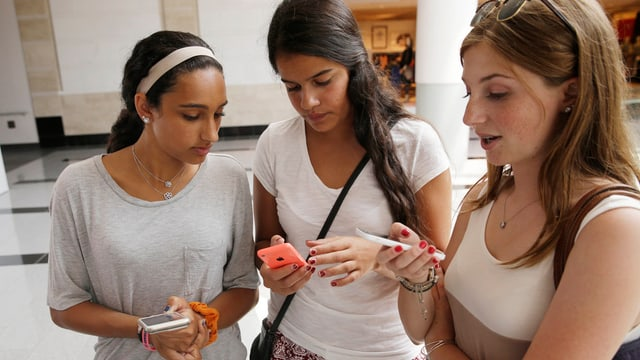 Drei junge Frauen gucken auf ihr Smartphone.