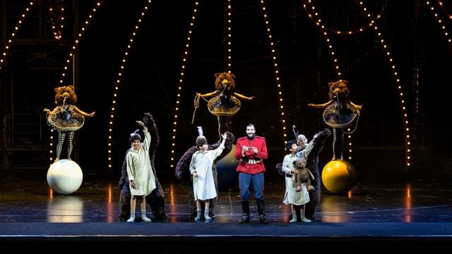Blick auf die Bühne. Akrobaten tanzen auf grossen Bällen. Musiker stehen vor ihnen.
