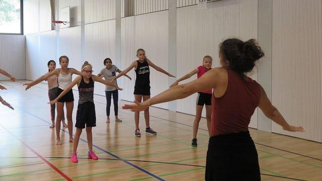 Eine Tanzlehrerin zeigt Mädchen in einer Turnhalle vor, was sie tanzen sollen.