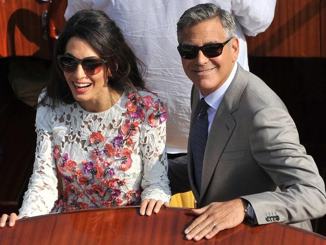 Amal Alamuddin (links) und George Clooney lächeln nebeneinander stehend auf einem Boot