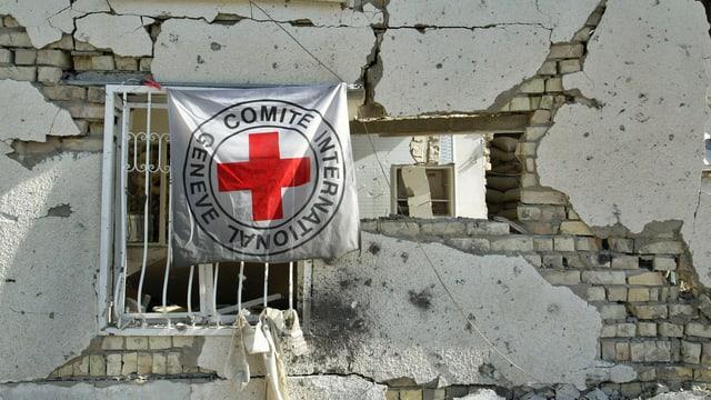 Eine IKRK-Fahne an einem zerstörten Gebäude in Bagdad (Archiv).