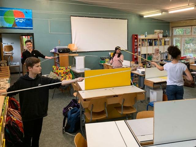 Schulkinder mit dem Stockmass im Klassenzimmer.