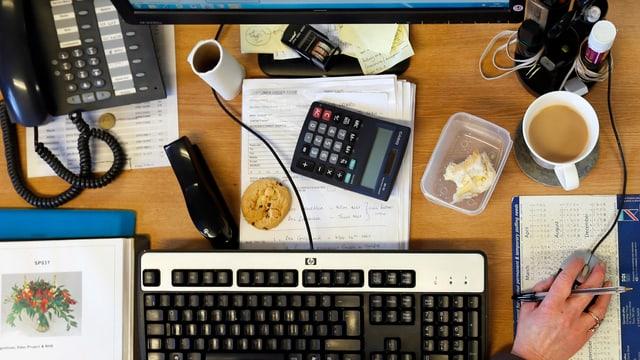 Pult mit Tastatur, Kaffee, Telefon und Taschenrechner.