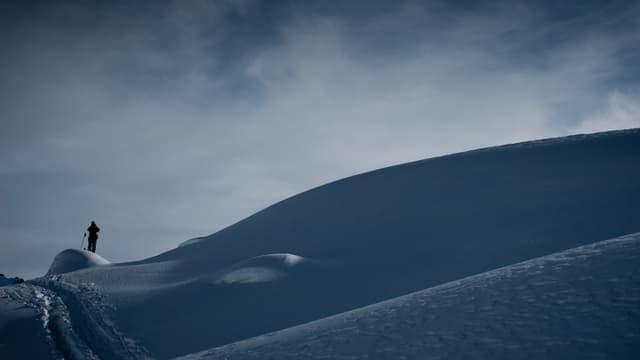 Skifahrer auf einem verschneiten Hügel.