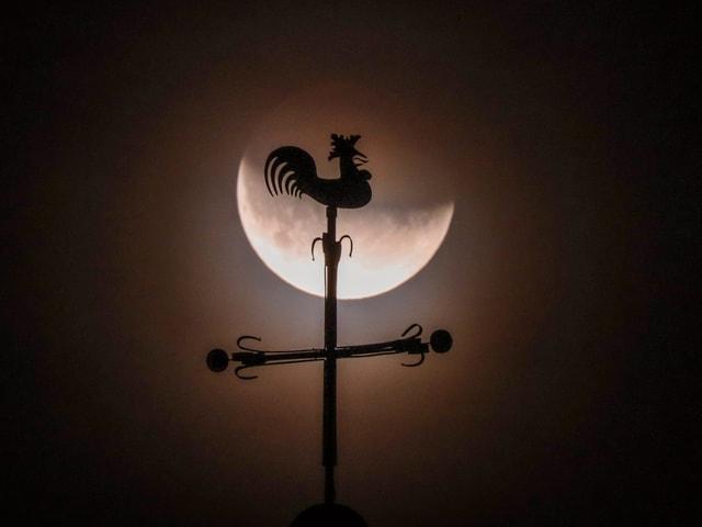 Mond hinter Hahn auf Kirche.