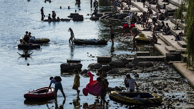 Menschen am Flussufer mit Gummibooten und aufblasbaren Ringen.