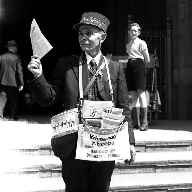 Ein Zeitungsverkäufer hält die NZZ in der Hand.