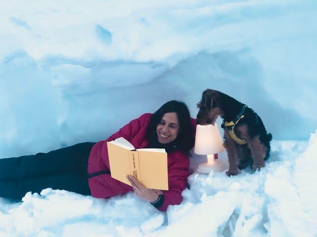 Annette König liegt im Schnee und liest den Roman «Mädchen, Frau etc.» von Bernardine Evaristo