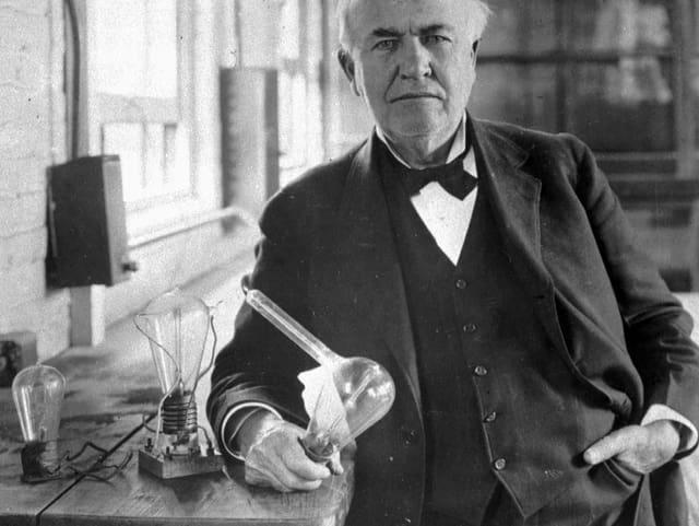 Thomas Alva Edison hält eine Glühbirne in der Hand.