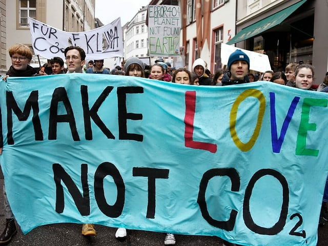 """Demonstrierende halten ein Plakat, worauf steht; """"Make love, not CO2""""."""