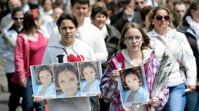 Weiss gekleidete Leute tragen Maries Porträt