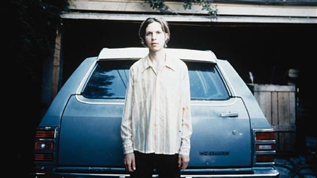 Der Künstler Beck vor einem alten Auto.