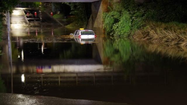 Hochwasser. Ein Taxi steht bis unters Dach im Wasser.