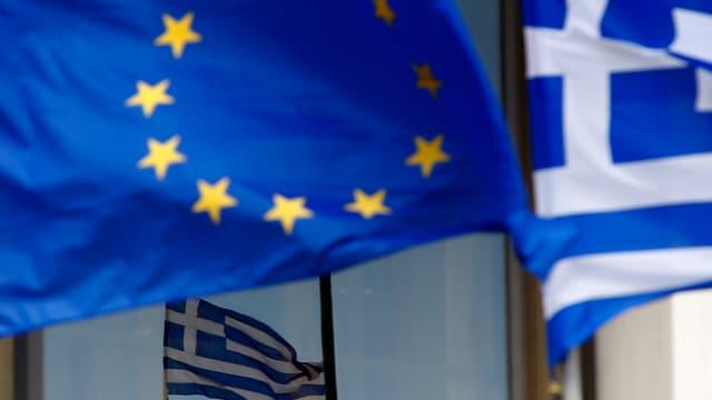 EU-Fahne weht neben zwei Griechenfahnen