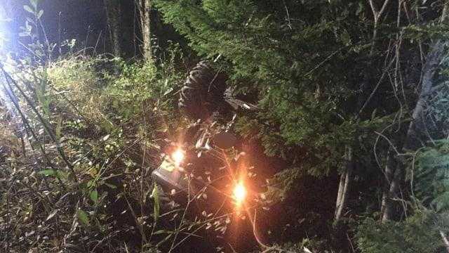 Das verunglückte Quadfahrzeug zwischen Bäumen und Sträuchern in einem Wald.
