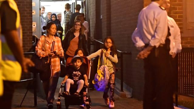 Frauen und Kinder kommen zu einer Tür hinaus, Sicherheitsläute kehren ihnen den Rücken zu.