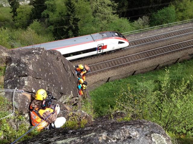 Kameramann hängt oben im Felsen, unten sind zwei weitere Personen angeseilt. Direkt darunter eine Bahnschiene mit einem vorbeifahrenden Zug.