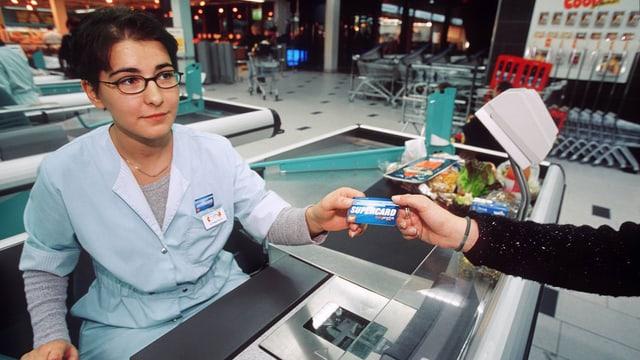 Eine Kundin überreicht einer Coop-Kassierin ihre Supercard