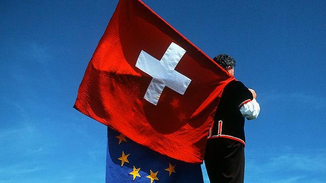 Mann in Sennentracht schultert eine Schweizer und eine EU-Fahne vor blauem Himmel.