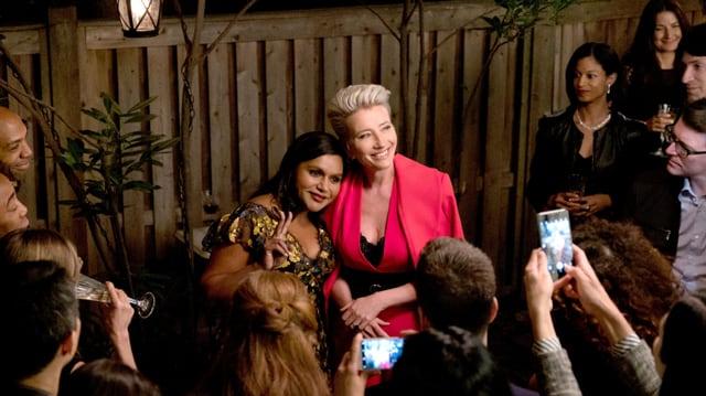 Zwei Frauen blicken Arm in Arm in Richtung der Journalisten und lächeln.