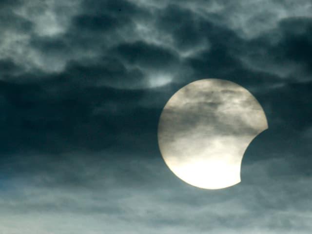 Die Sonnenscheibe hat auf der rechten unteren Seite eine merkwürdige Abschattung. Vor der Sonne hat es zum Teil Wolken.
