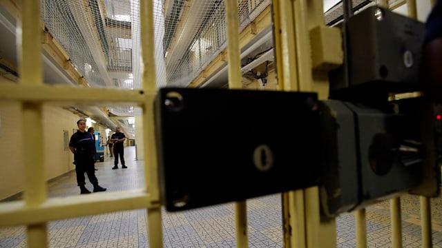 Blick durch eine Gefängnistüre durch, Wärter im Hintergrund.