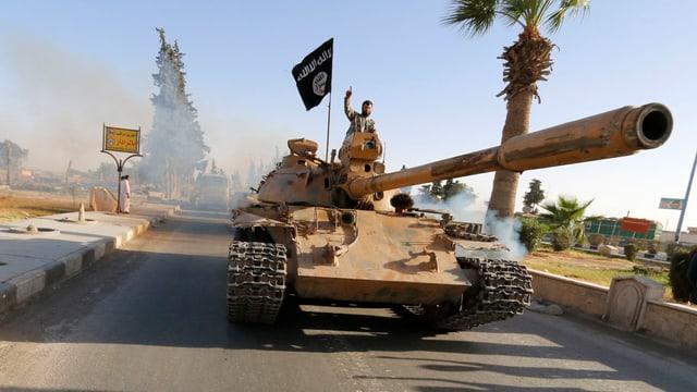 An Mann mit in die Höhe gestrecktem Finger fährt auf einem Panzer, neben ihm die schwarze Fahne der IS.