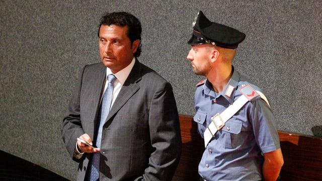 Kapitän Schettino steht neben einem Polizisten im Gericht von Grossetto.
