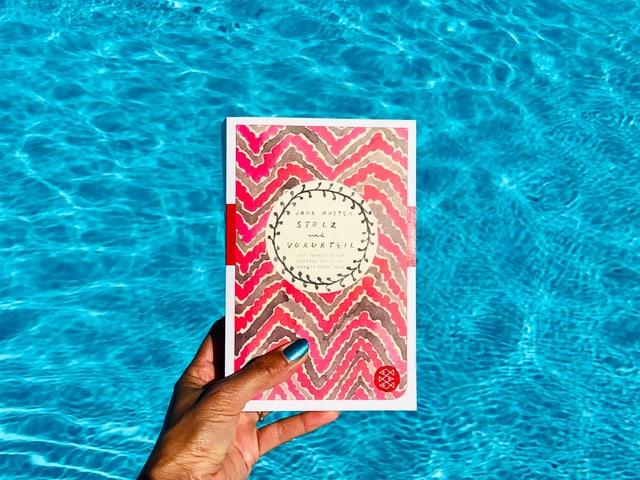 Der Roman «Stolz und Vorurteil» von Jane Austen vor leuchtend blauem Wasser