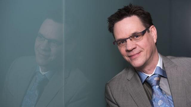 Ein Mann mittleren Alters im grauen Anzug und Krawatte lächelt.