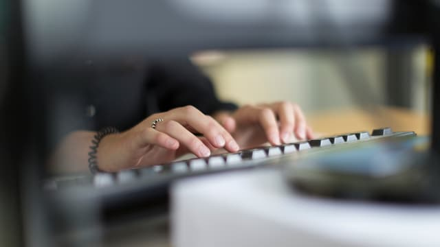 Frauenhände an einer Tastatur.