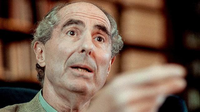 Der Autor Philip Roth schaut in die Kamera und gestikuliert.