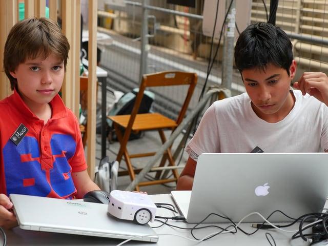 Zwei Jungen sitzen vor Laptops, auf dem einen, zugeklappten Laptop steht ein kleiner, weisser Roboter.