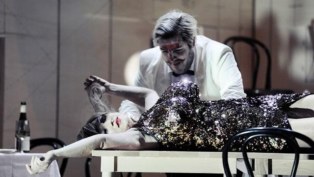 Ausschnitt aus «La Traviata»: Svetlana Doneva liegt als Violetta mit goldenem Kleid auf einem Tisch - dahinter steht ein Diener mit weissem Kittel.