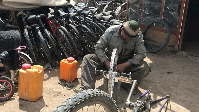 Mann flickt ein Velo. Dahinter stehen andere Fahrräder.