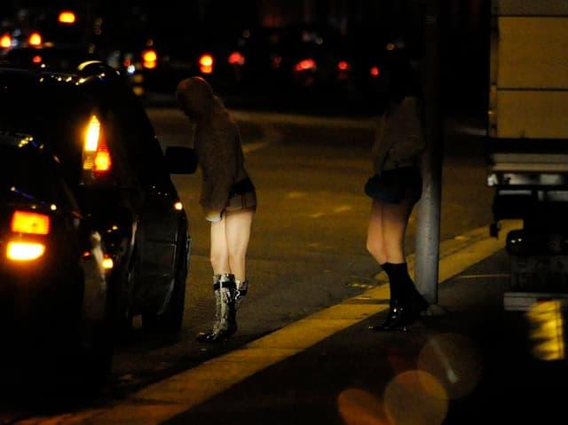 Zwei Prostituierte in hohen Stiefeln stehen im Dunkeln an der Strasse.