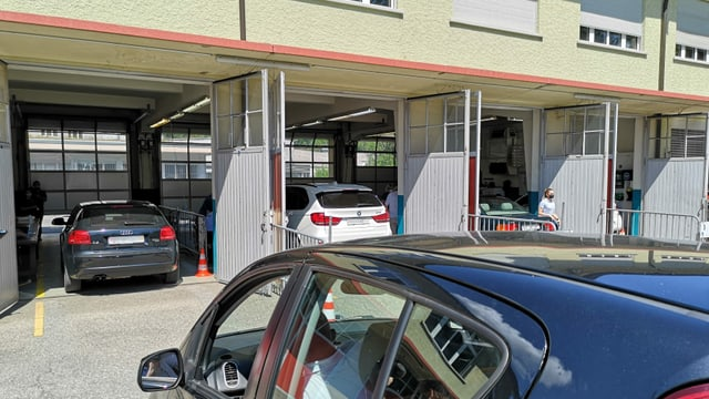Autos stehen in Garage mit beidseitigen Toren.