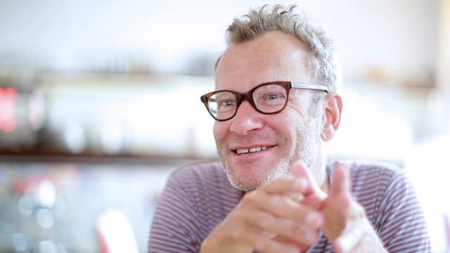 Ein Mann mit Hornbrille und kurzen Haaren lächelt.