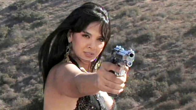 Eine leichtbekleidete mexikanische Frau zielt mit einer Pistole auf ein nicht sichtbares Gegenüber.