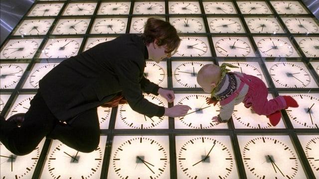 Eine Frau und ein Baby hocken auf einer Installation in einem Museum bestehend aus Uhren
